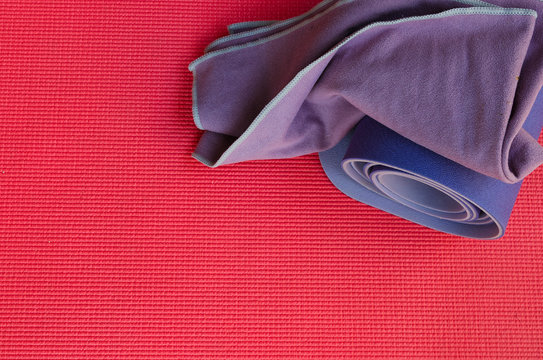 Essential yoga props, rolled lilac exercise mat and towel on bright pink yoga mat background.