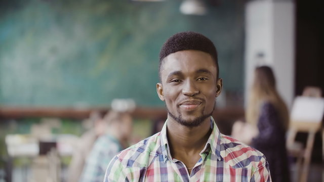 Handsome african man at busy modern office. Portrait of young successful male looking at camera and smiling.