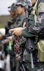 A member of the PNP Special Action Force holds a bunch of rosary beads and a bible during a mass inside a police camp in Bicutan city