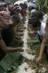 Residents eat lunch along the busy streets of Taguig city, east of Manila