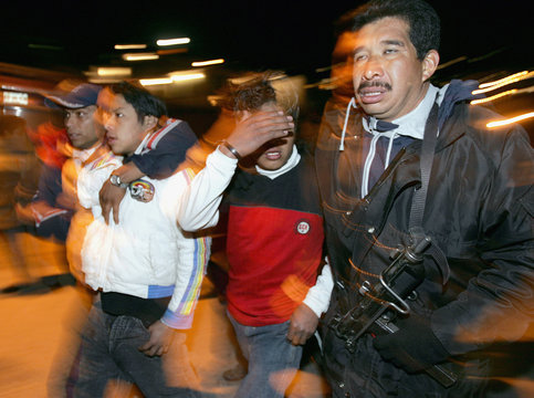A Mexican police officer escorts two suspected burglars in a poor village in the Naucalpan district