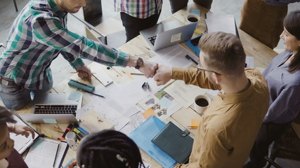 Top view of young business team working together near the table, brainstorming. Two mans fist greeting each other. Wall mural