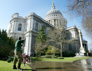 A GARDENER LOOKS AT THE RESTORED EAST FACE OF ST PAUL'S CATHEDRAL IN LONDON.