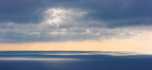 Magic seascape in the evening. Sun glare on the surface of the water and soft tones of the sky with clouds.