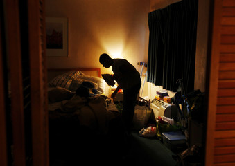 Fourteen-year-old Handsom irons his shirt before work in the early morning at a motel in Cambridge