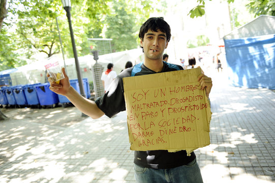 A drunk man carrying a sign asks for money on a street during the San Fermin festival in Pamplona