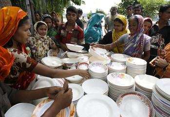 Women examine crockery before buying from a street vendor in Dhaka