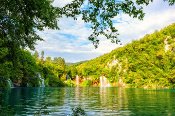 Lovely creek with crystal clear water in the Plitvice Lakes National Park surrounded by green grass and trees, famous place in Croatia, nature background