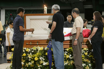 Relatives and supporters sprinkle holy water at flag-draped coffin of former Philippine President Aquino during wake in San Juan