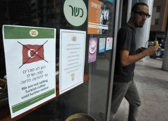 Sign depicting crossed out Turkish flag is taped to window of coffee shop in Tel Aviv