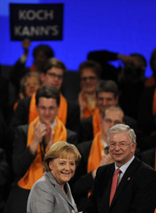Hesse's state PM and top candidate for CDU Roland Koch and German Chancellor Angela Merkel react after an election campaign in Frankfurt