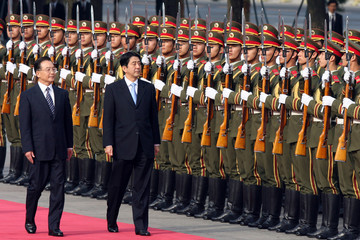 Japanese Prime Minister Abe and Chinese counterpart Wen review the honour guard during a welcome ceremony at the Great Hall of the People in Beijing