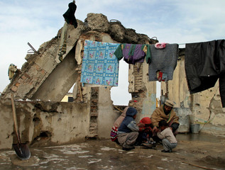 Afghan family sit around a fire in a destroyed building in Kabul