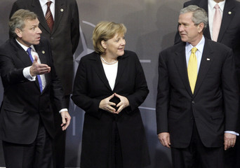US President Bush speaks with German Chancellor Merkel and NATO Secretary Scheffer during official photo with NATO Heads of State and Government in Riga, Latvia