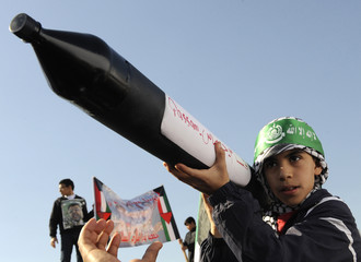 A boy in Kuwait holds a toy rocket launcher during a demonstration against Israel's offensive in Gaza, in Kuwait City