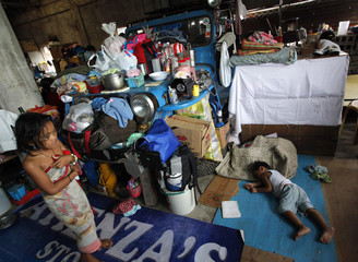 A boy sleeps by a jeepney converted into a makeshift dwelling inside an evacuation center for victims hit by floods caused by Typhoon Ketsana in Rizal