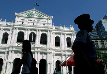 TOURIST AND POLICEMAN WALK PAST PORTUGUESE STYLE BUILDING IN MACAU.