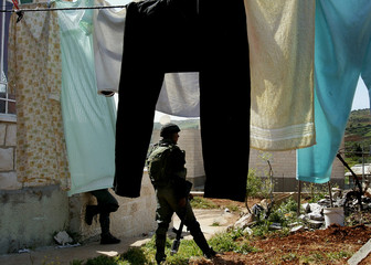 AN ISRAELI BORDER POLICEMAN GUARDS THE FRONT OF A PALESTINIAN HOUSE DURING A PROTEST IN THE WEST BANK.