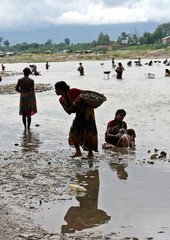 A woman labourer carries stones on the banks of the Balason river in Siliguri