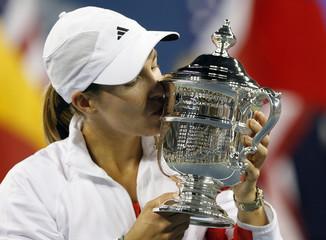 Justine Henin of Belgium kisses the trophy after defeating Svetlana Kuznetsova of Russia in the women's final of the U.S. Open tennis tournament in New York