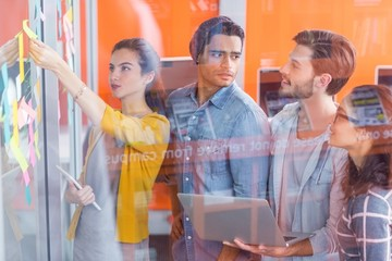 Executives discussing over sticky notes on glass wall