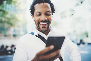 Closeup view of Happy american African man using smartphone outdoor to texting a sms message with friends.Portrait of young black cheerful man listining to music.Blurred background, horizontal.