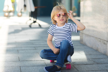 Pretty little boy on a skate board. Emotional kid outdoors. Cute child skating wearing sunglasses.