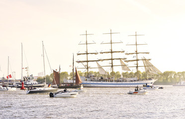Hamburg harbor, birthday parade with various ships. View to a ship parade in the evening sun or sunset.