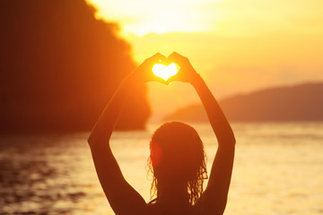 Heart shape making of female hands against bright sea sunset and sunny islands on horizon line