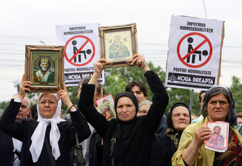 Romanians hold Orthodox icons and anti-homosexuals signs during a protest against a scheduled gay pa..