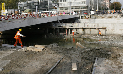 A construction worker gestures while the new Gessnerbruecke bridge is being moved to its final position over the Sihl river in Zurich