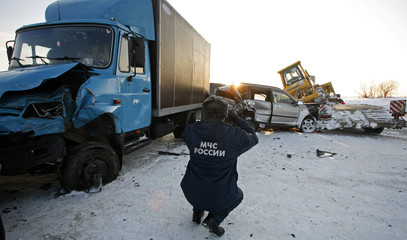 A rescue worker takes pictures of cars wedged into each other after accident involving 17 vehicles near Krasnoyarsk