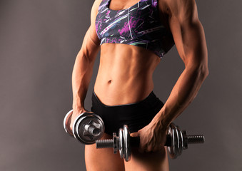 Muscular beautiful healthy young fitness model woman athlete standing posing in sportswear top and shorts and doing workout with high weight dumbbells. Close up, isolated on gray lifestyle image.