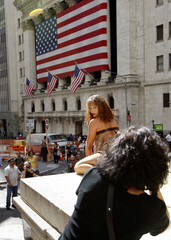 People stop and stare as a model poses for an impromptu photo shoot on the steps of Federal Hall, in front of the New York Stock Exchange