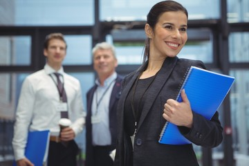 Happy businesswoman standing with spiral book