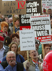 People hold banners as they protest against unpopular new labour and welfare reforms of the German ...