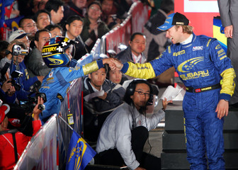 Subarus driver Petter Solberg shakes hands with Japanese boy at ceremonial start of Rally of Japan in Obihiro