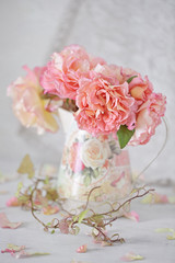 Beautiful garden roses in a jug on a table .