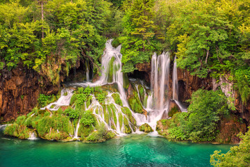 Beautiful waterfall in a green forest, Plitvice Lakes National Park, famous tourist destination in Croatia, nature background suitable for wallpaper, cover or guide book