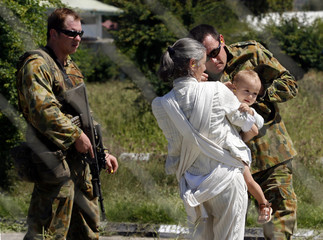 Australian military personnell assist child with ear plugs while evacuating expatriates in Dili