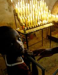 CUBAN BOY NEXT TO BURNING CANDLES AT VIRGIN OF COBRE CHURCH.