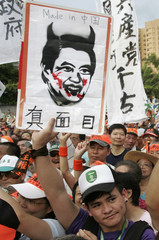 A protester holds a portrait of Taiwan's President Ma Ying-jeou with devil horns as he takes part in a rally outside the Presidential Office in Taipei