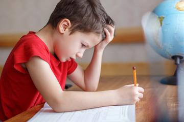 Sad little boy depressed while doing homework