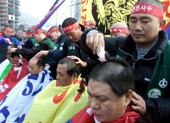SOUTH KOREAN UNION LEADERS CUT THEIR HAIR DURING PROTEST IN SEOUL.