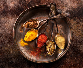 Powder spices and herbs in spoons on a grunge texture