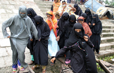 Bangladeshi garment workers in veils board boats to cross Buriganga river for jobs in factories ...