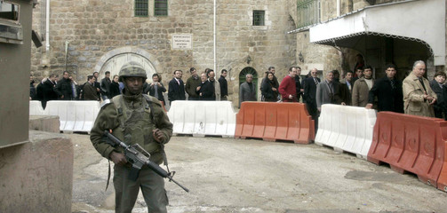 An Israeli border policeman stands guard as a group of foreign diplomats visits Hebron