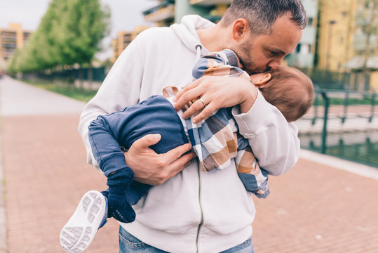 Dad hugging son outdoor park kissing