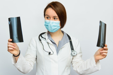 Young female doctor looking at the x-ray picture no white background