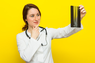 Young female doctor with stethoscope looking at the x-ray picture on yellow background